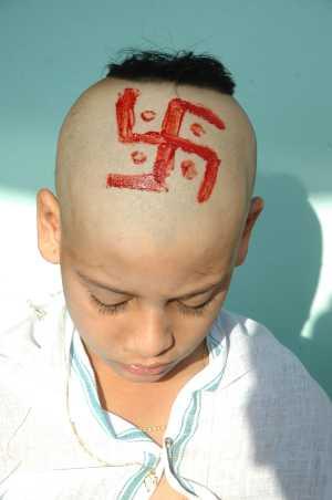 símbolo pintado no topo da cabeça de garoto Hindu durante um ritual de iniciação